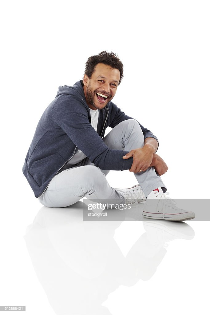 Portrait of cheerful african man sitting on white : Stock Photo