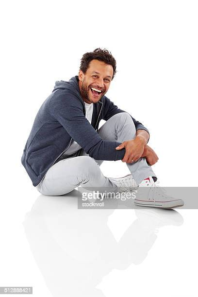 Portrait of cheerful african man sitting on white