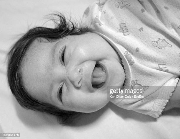Portrait Of Cheerful Baby Lying On Bed