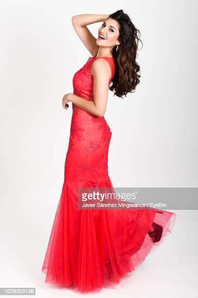 portrait of cheerful beautiful model wearing red evening gown against white background - evening gown stock pictures, royalty-free photos & images