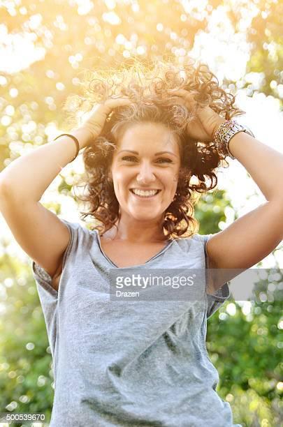 Porträt von fröhlich schöne Frau mit lockigem Haar auf Natur