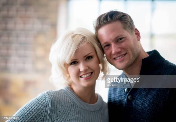 Portrait de couple gai à la maison en regardant caméra souriant tandis que l'homme est embrassant son partenaire
