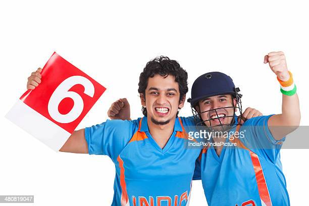Portrait of cheerful cricket fans in jerseys over white background