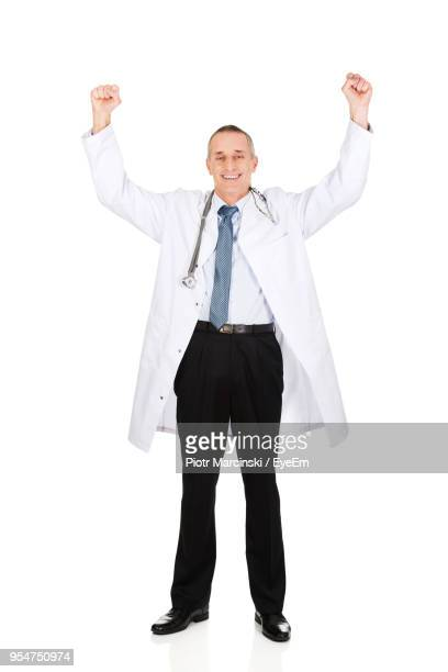 portrait of cheerful doctor with arms raised against white background - laborkittel stock-fotos und bilder