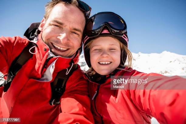Portrait of cheerful father and daughter in warm clothing
