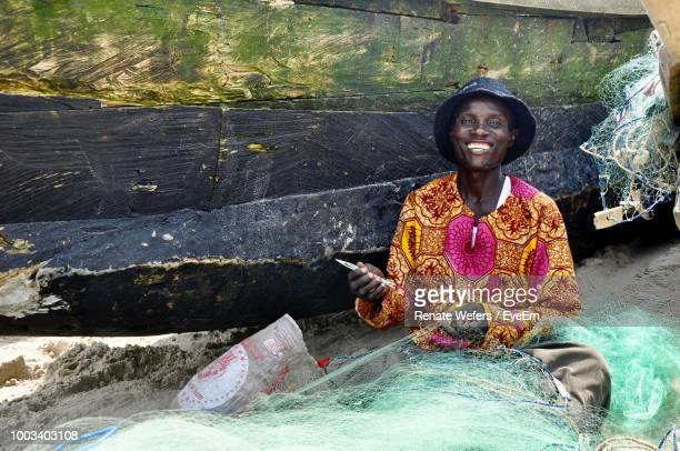 portrait of cheerful fisherman with net at beach - ghana stock pictures, royalty-free photos & images