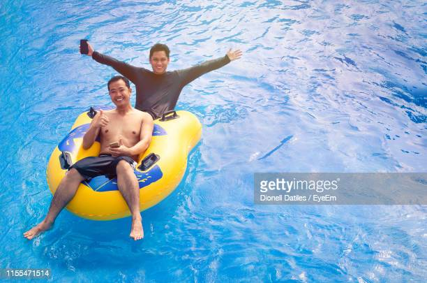 portrait of cheerful friends in swimming pool - male friendship stock pictures, royalty-free photos & images