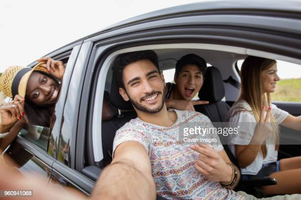 portrait of cheerful friends on road trip - four people in car stock pictures, royalty-free photos & images