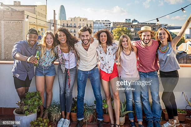 Portrait of cheerful friends standing on terrace