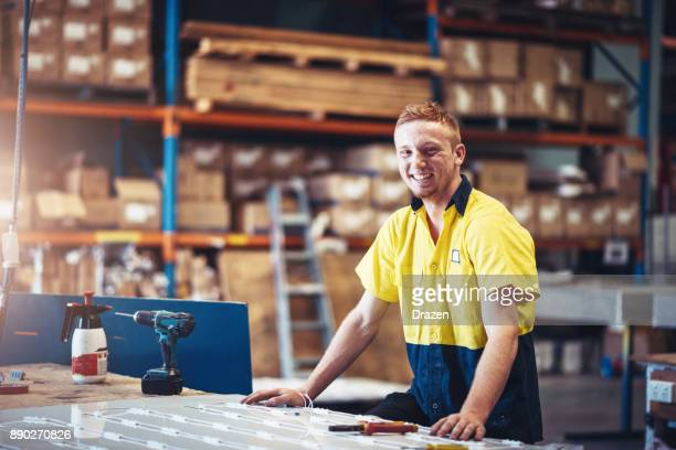 Portrait of cheerful ginger blue collar worker in factory in Australia