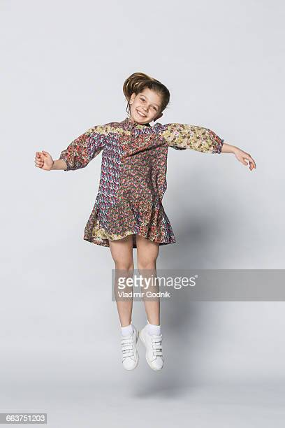 Portrait of cheerful girl jumping against white background
