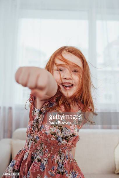 portrait of cheerful girl punching while standing against sofa in living room - colpire con un pugno foto e immagini stock