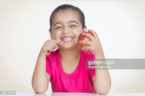 Portrait of cheerful girl showing fresh apple against colored background