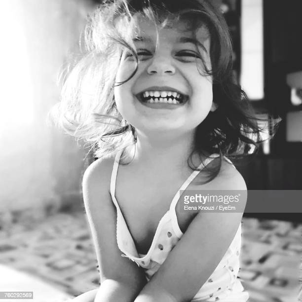portrait of cheerful girl sitting on bed at home - elena knouzi stock pictures, royalty-free photos & images