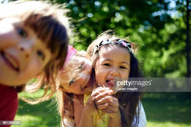 portrait of cheerful girls during birthday celebration at park - nur kinder stock-fotos und bilder