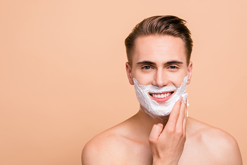 Portrait of cheerful, handsome, attractive man smearing foam for shave on his face looking at camera isolated on beige background 1049751930