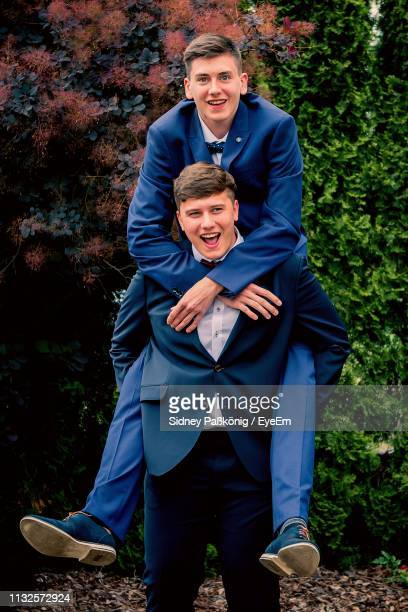 Portrait Of Cheerful Man Piggybacking Male Friend Against Plants