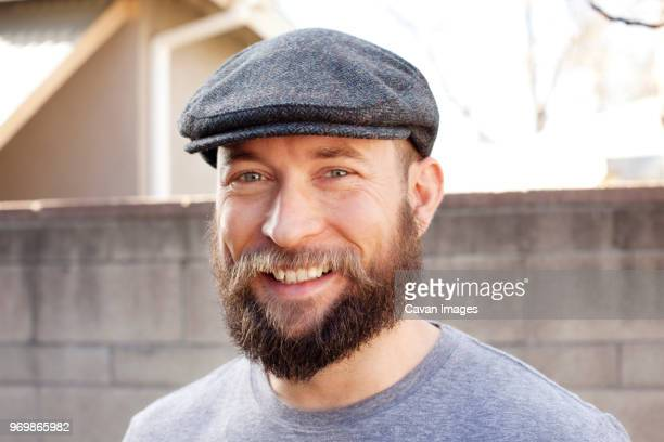 portrait of cheerful man standing against wall - flat cap stock pictures, royalty-free photos & images