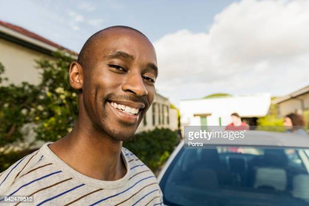 Portrait of cheerful man standing by car at yard