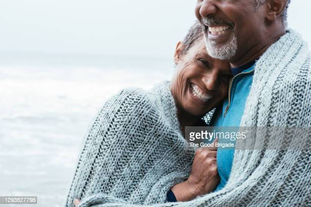 portrait of cheerful mature woman embracing partner at beach against sea - 中央部分 ストックフォトと画像