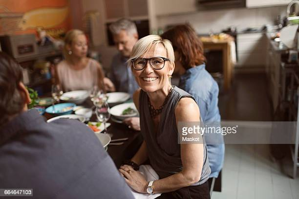Portrait of cheerful mature woman sitting with friends at table