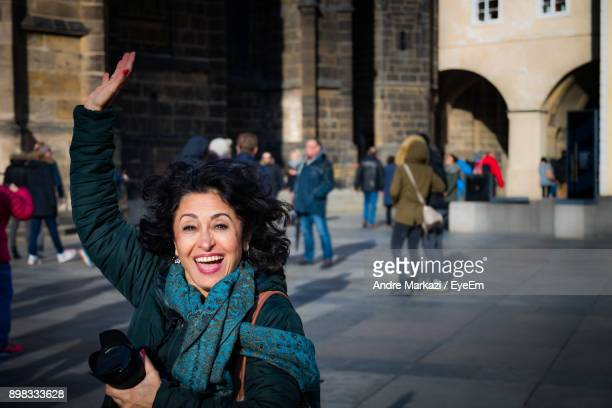 Portrait Of Cheerful Mature Woman With Arm Raised In City