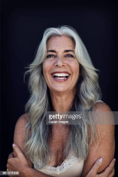 portrait of cheerful mature woman with long gray hair against blue background - belles poitrines photos et images de collection