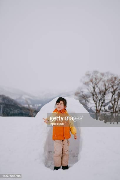 Portrait of cheerful mixed race preschool girl in front of igloo