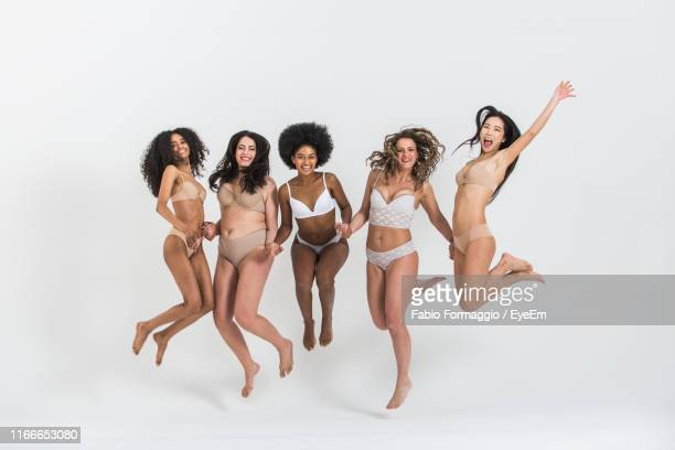 portrait of cheerful multi-ethnic women in lingerie jumping against white background - curvy asian woman stock pictures, royalty-free photos & images