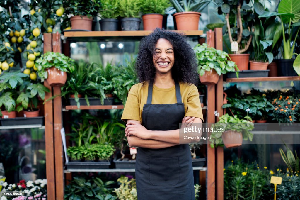Portrait of cheerful owner standing at market stall : Stock Photo