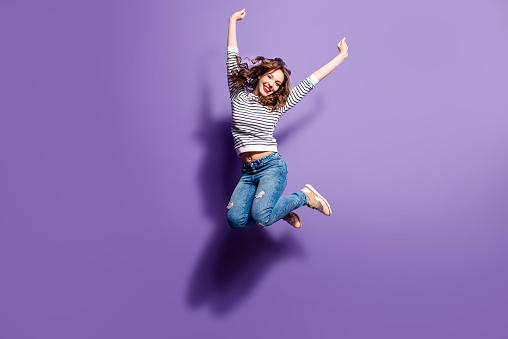 Portrait of cheerful positive girl jumping in the air with raised fists looking at camera isolated on violet background. Life people energy concept 971399898