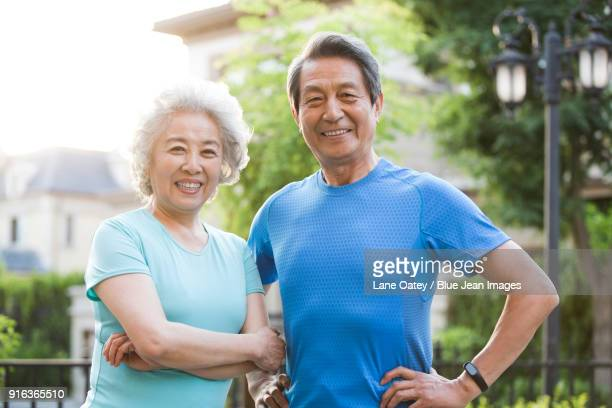 portrait of cheerful senior couple - arms akimbo stock pictures, royalty-free photos & images