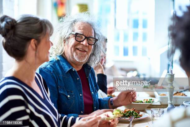 portrait of cheerful senior man enjoying healthy lunch with friends - enjoyment stock pictures, royalty-free photos & images