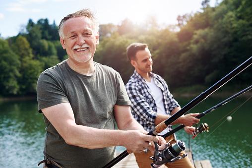 Portrait of cheerful senior man fishing 928819426
