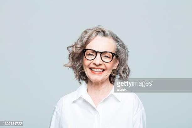 porträt einer fröhlichen seniorin im weißen hemd - izusek stock-fotos und bilder