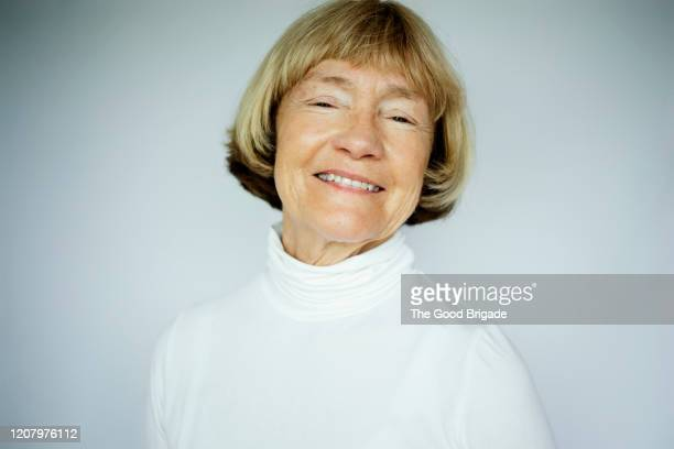 portrait of cheerful senior woman on white background - neckline stock pictures, royalty-free photos & images