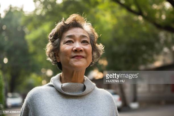 portrait of cheerful senior woman relaxing outdoor, standing on the road in the city - disruptaging foto e immagini stock