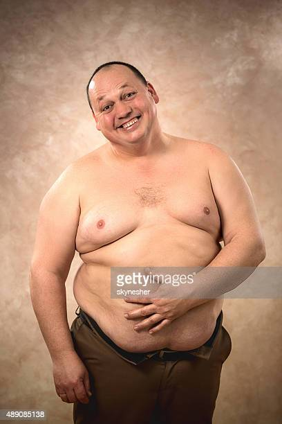 Portrait of cheerful shirtless fat man looking at camera.