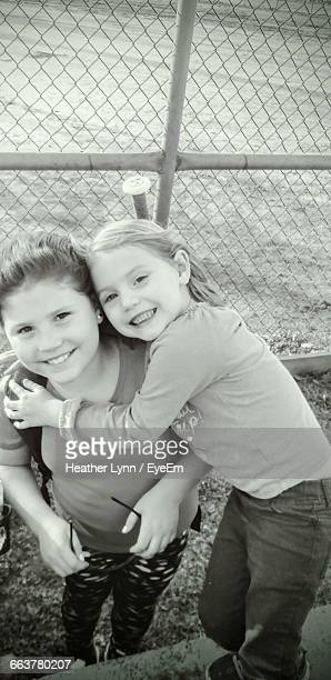 portrait of cheerful sisters embracing against chainlink fence - lynn pleasant stock pictures, royalty-free photos & images