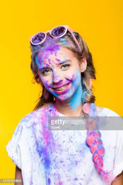 porträt von fröhlichen teenager-mädchen mit holi pulver bedeckt - izusek stock-fotos und bilder