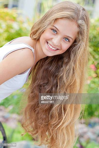 Portrait of cheerful teenage girl posing, smiling expressing positivity outdoors