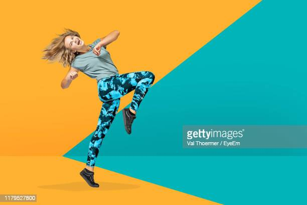 portrait of cheerful woman dancing against colored background - ツートンカラー ストックフォトと画像