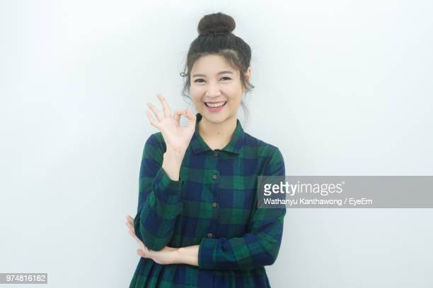 Portrait Of Cheerful Woman Gesturing Ok Sign Against White Background