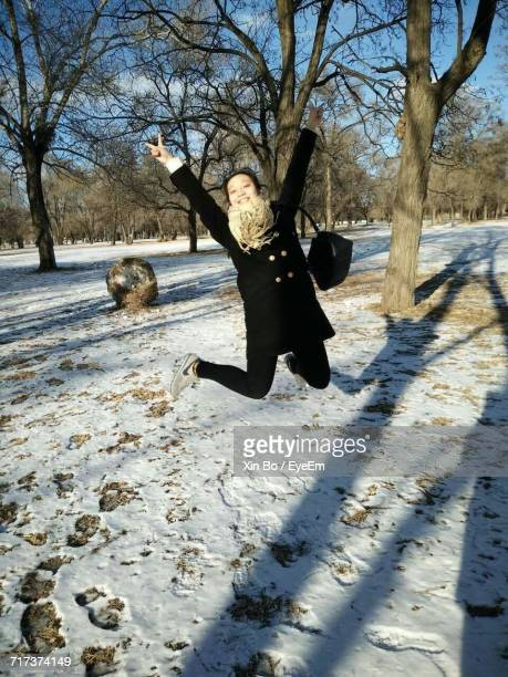 Portrait Of Cheerful Woman Jumping While Showing Peace Sign At Park During Winter