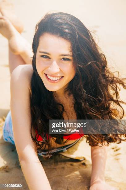 Portrait Of Cheerful Woman Lying At Beach