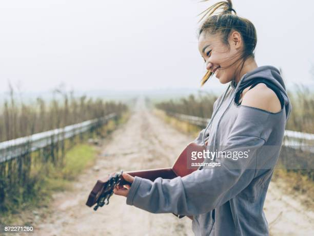 portrait of cheerful woman playing guitar at country road