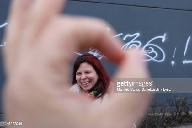 portrait of cheerful woman seen through human hand sign outdoors - schlebusch stock pictures, royalty-free photos & images