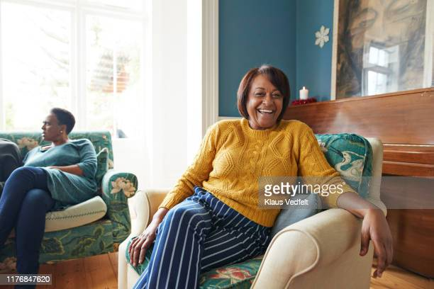 portrait of cheerful woman sitting on armchair - selective focus stock pictures, royalty-free photos & images