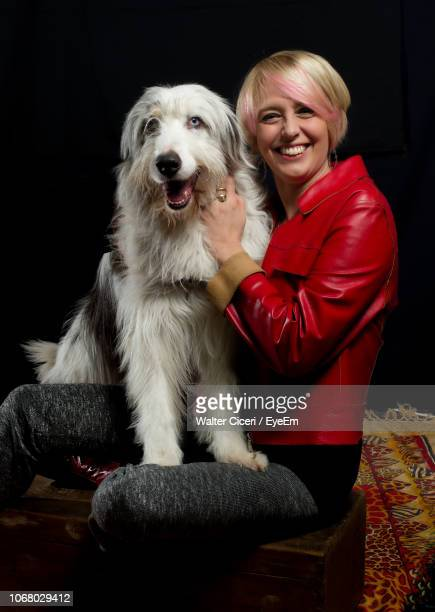 portrait of cheerful woman sitting with dog against black background - walter ciceri foto e immagini stock
