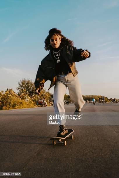 portrait of cheerful woman skating on road in park - eislauf oder rollschuhlauf stock-fotos und bilder